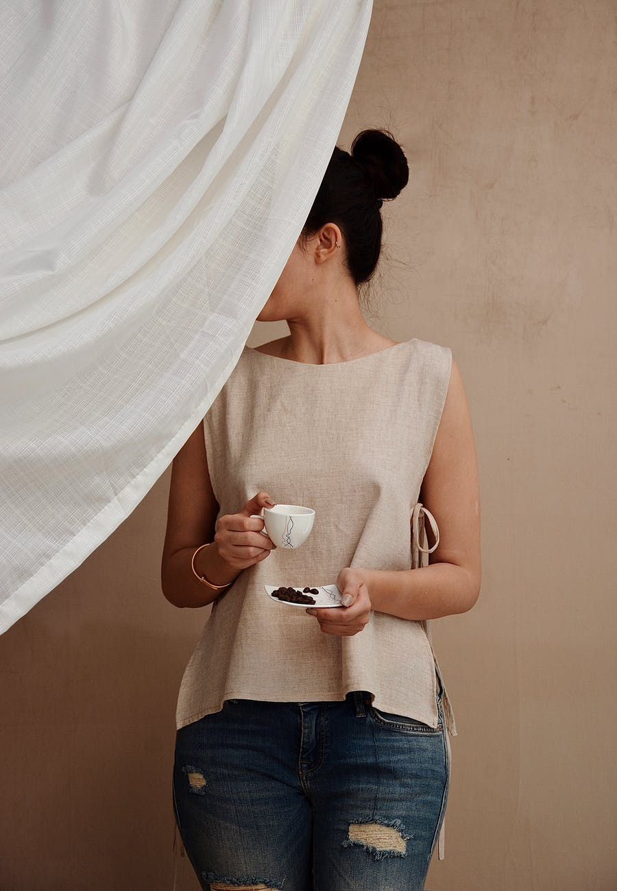 anonymous stylish woman with cup of coffee behind fabric